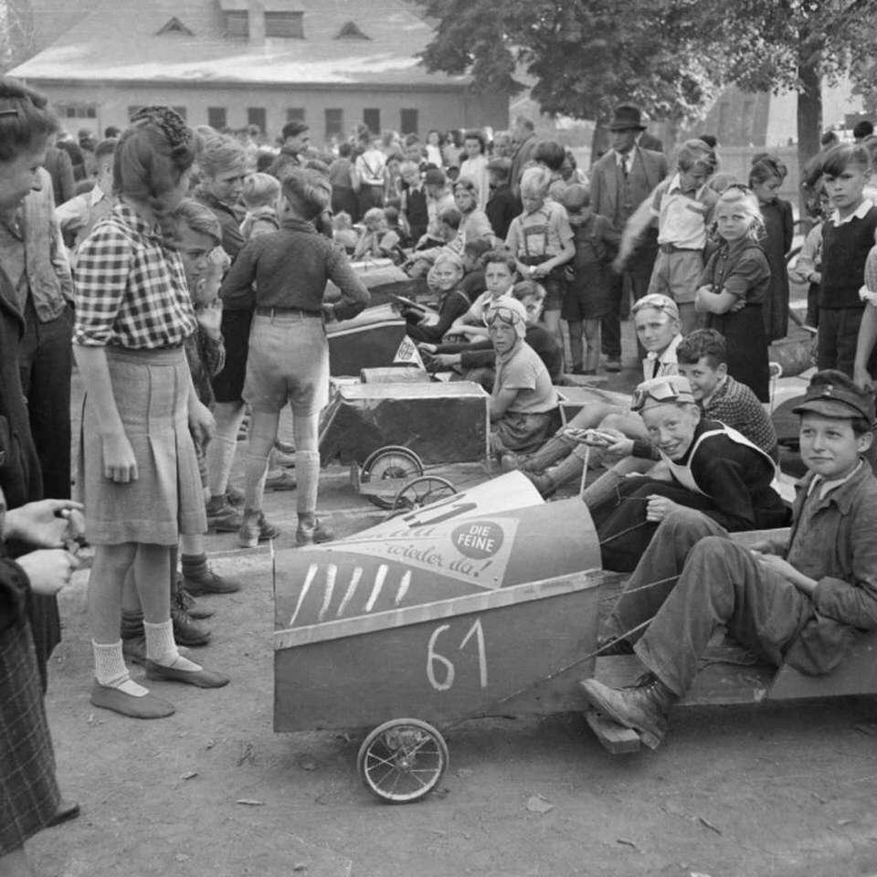 Menschenmenge mit Kindern in Seifenkistenautos