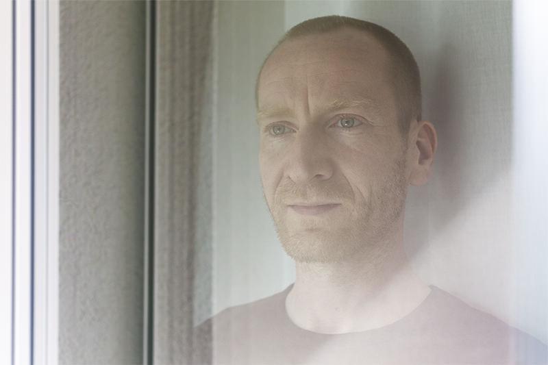 Männerportrait hinter einer Glasscheibe