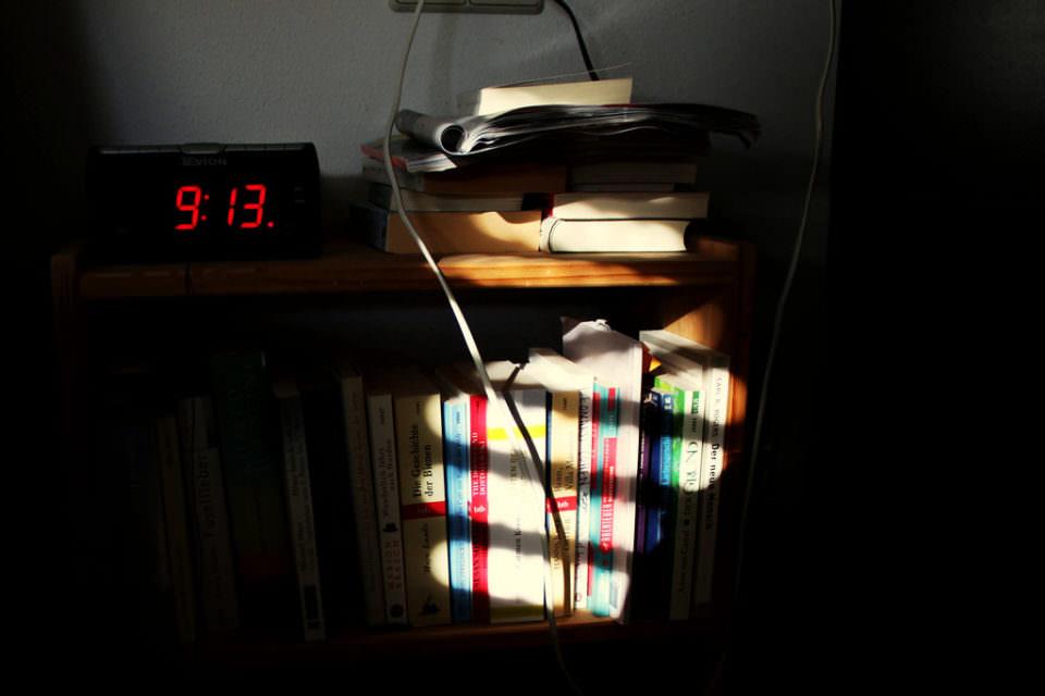 Blick auf einen Wecker und Bücher