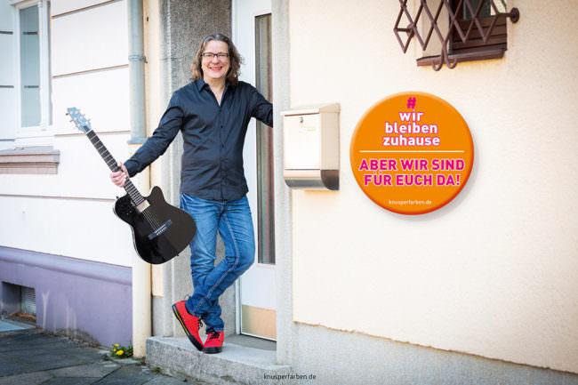 Mann mit Gitarre an einer Haustür