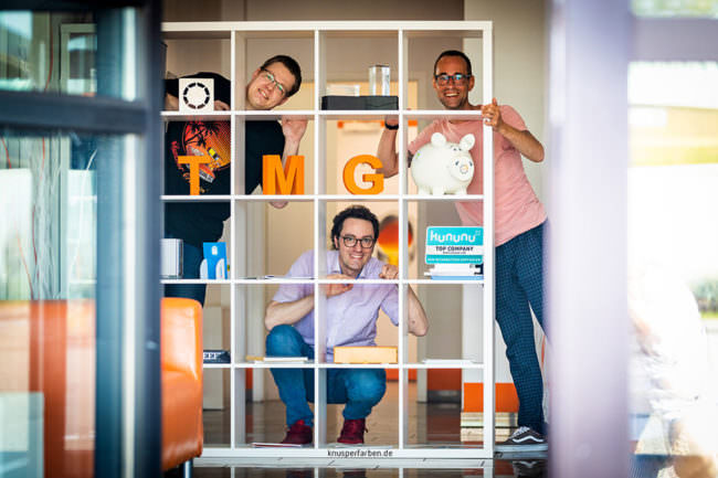 Drie Personen schauen durch ein Regal