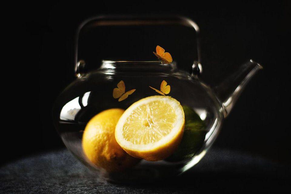Zitronen und Schmetterlinge in einer Teekanne