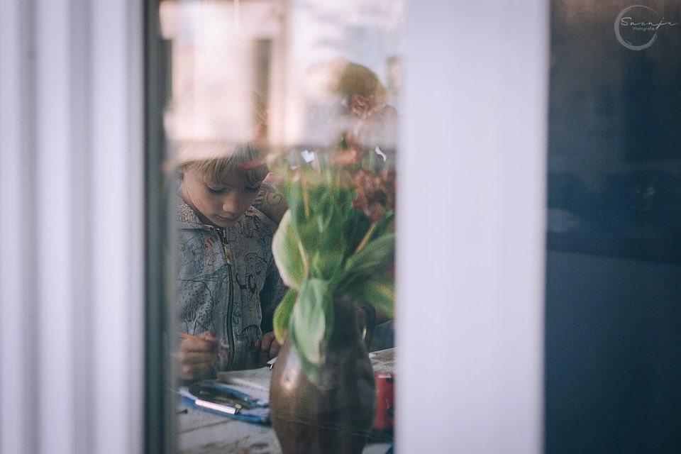 Blick durch ein Fenster mit Blick auf einen Jungen beim Schreiben