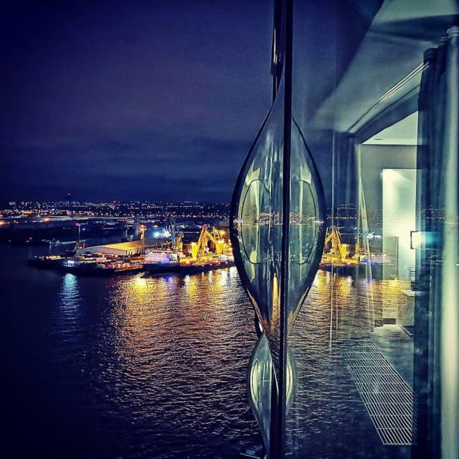 Blick durch ein Fenster auf einen Hafen bei Nacht