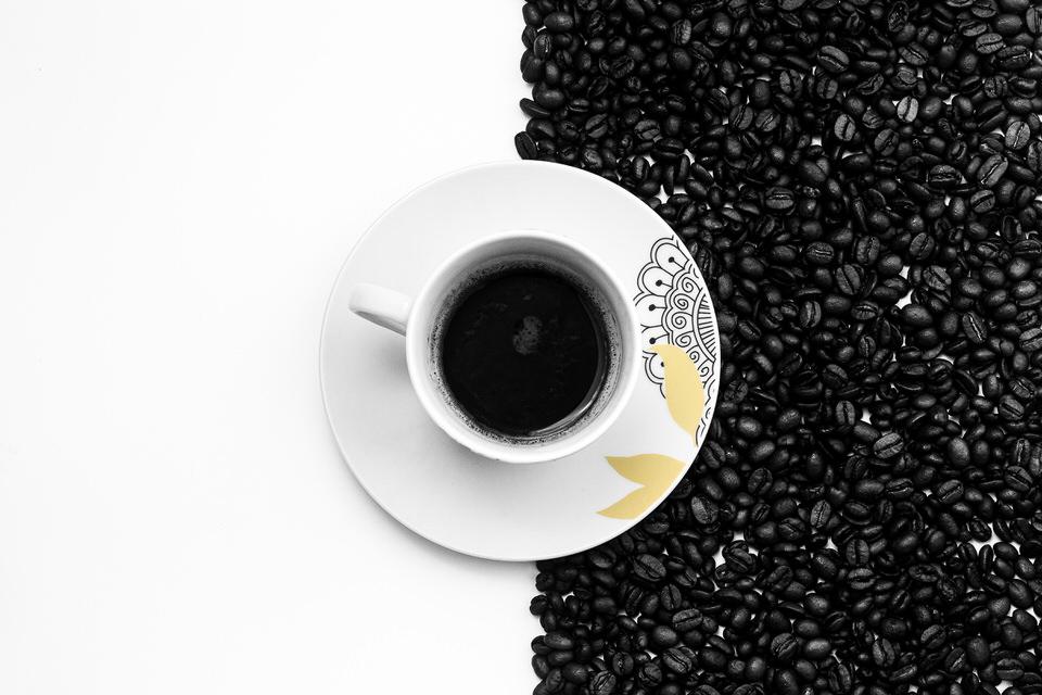 Kaffeetasse mit Kaffeebohnen auf einer Seite