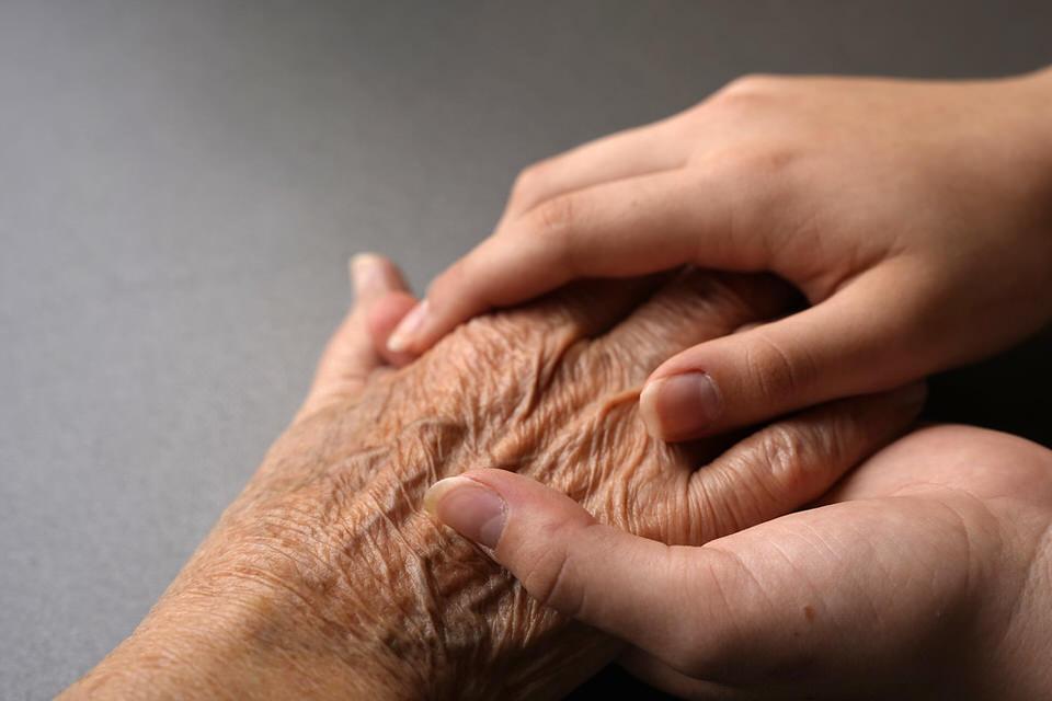 Junge Hände auf einer älteren Hand