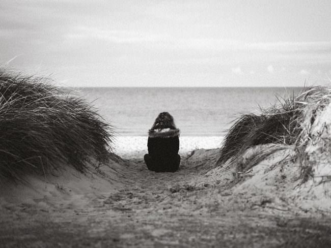 Frau sitzt am Strand