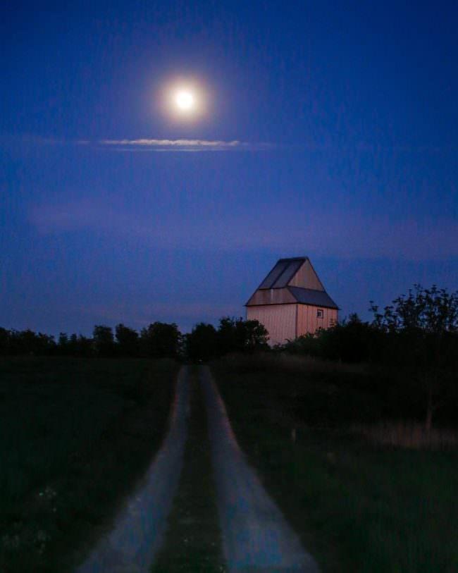 Landschaft mit Gebäude und Mond
