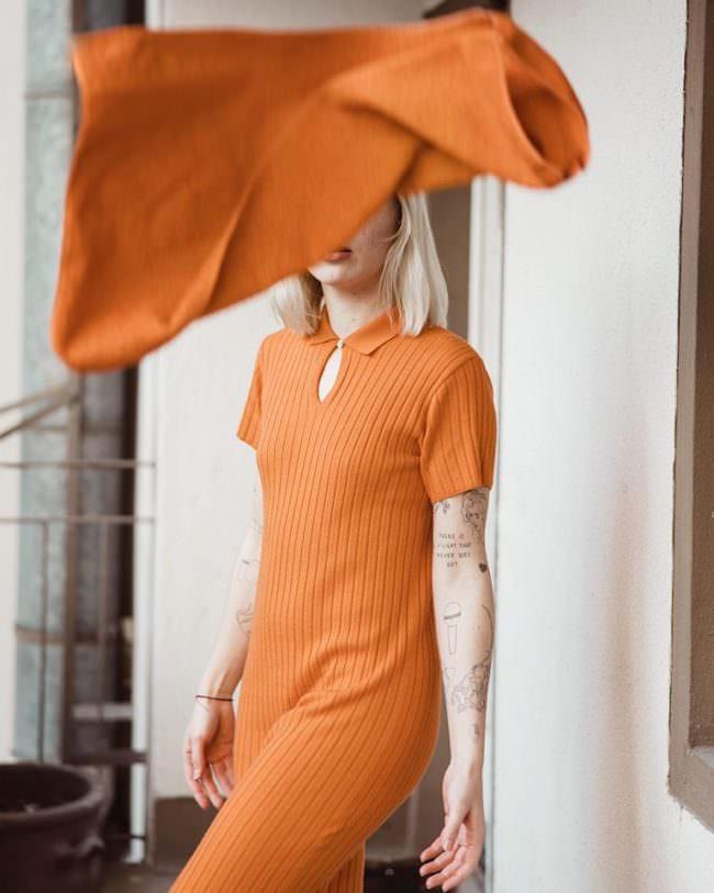 Portrait Frau mit orangem Kleid, Gesicht verdeckt von orangem Stoff
