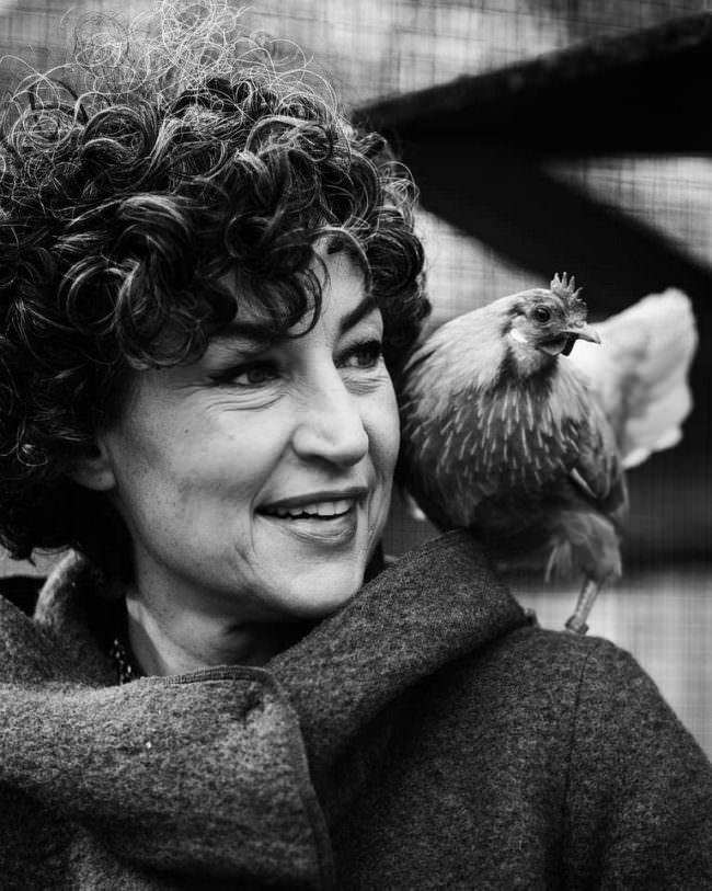 Portrait einer Frau mit Huhn auf der Schulter