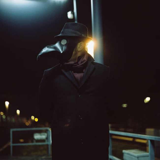 Portrait mit Pestmaske im Dunkeln