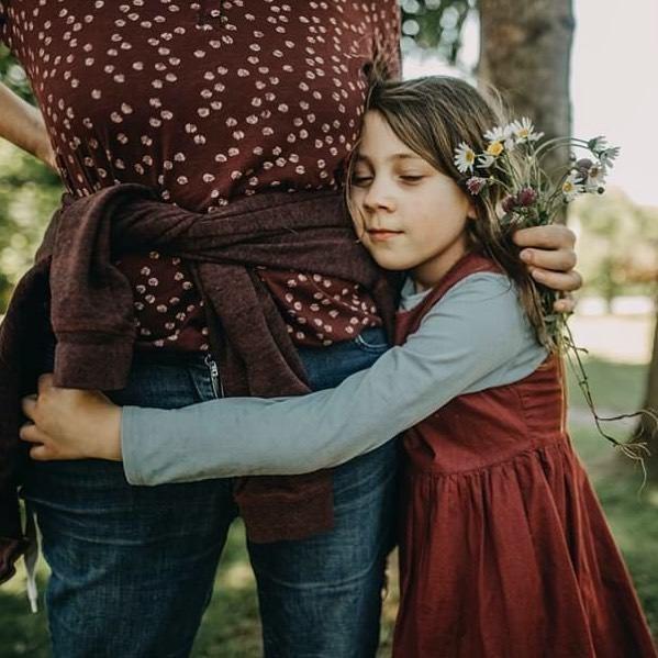 Kind umarmt eine Person, die Blumen trägt