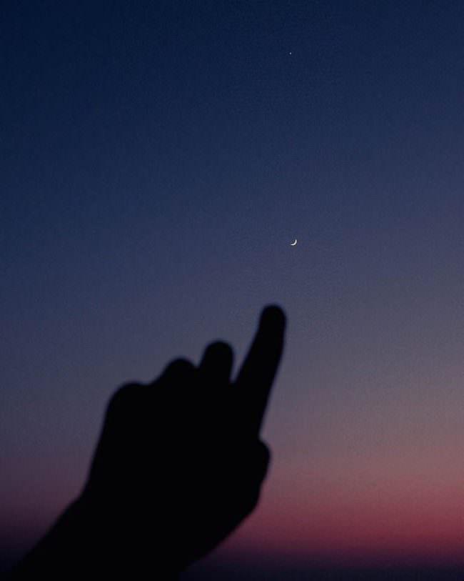 Hand deutet auf Mond am Himmel