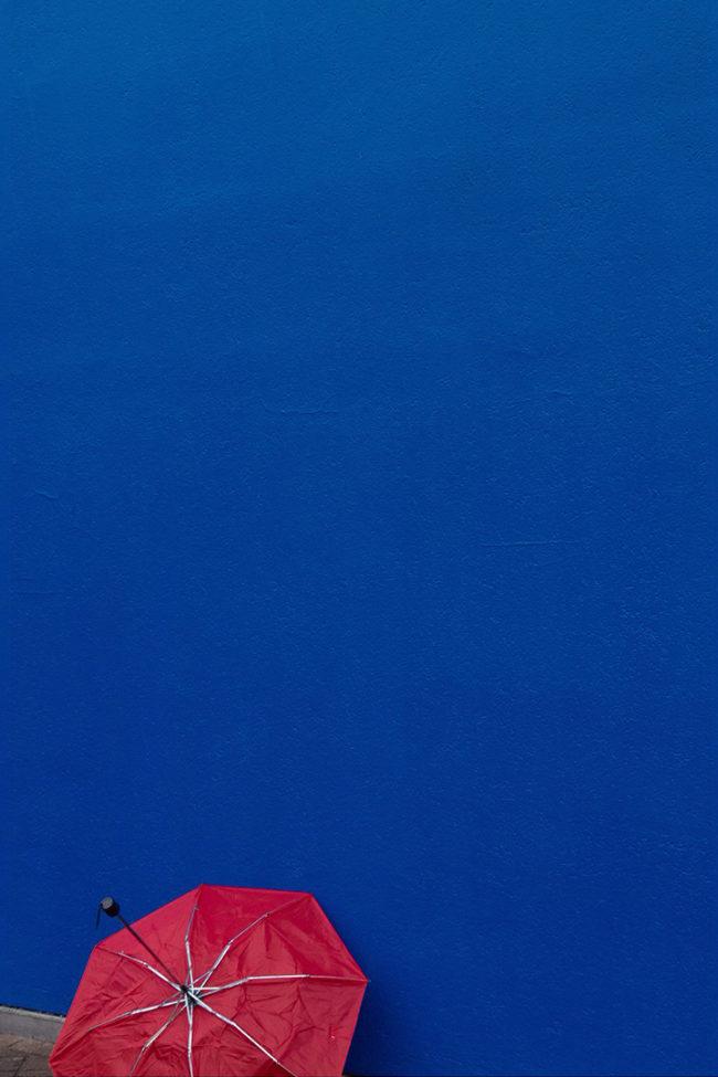 Roter Regenschirm vor blauer Wand