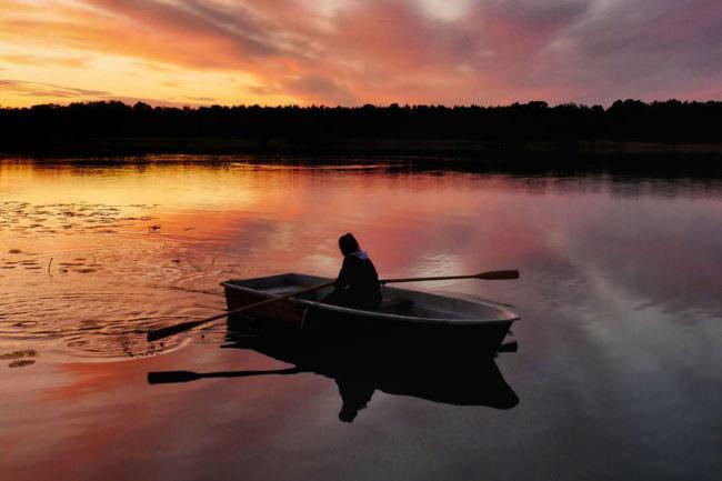Person mit Ruderboot im Sonnenuntergang