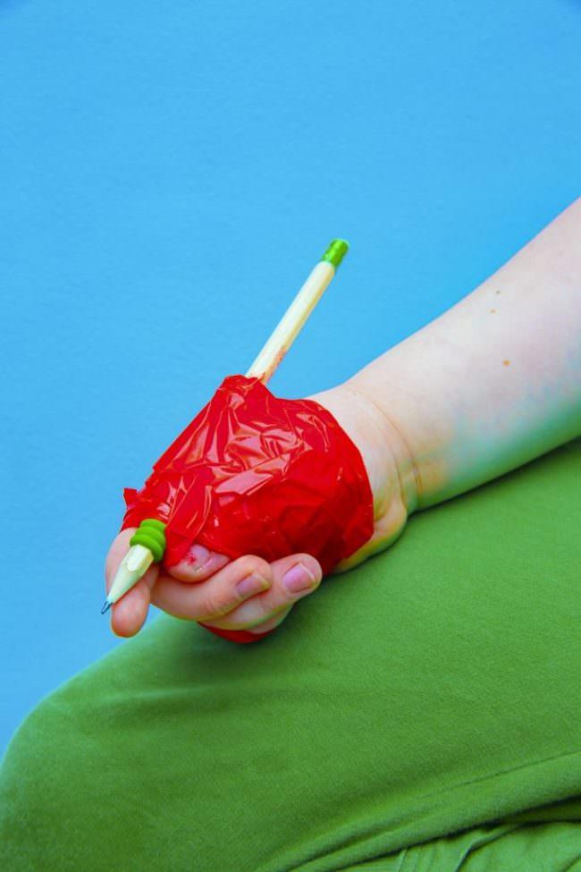 Stift mit rotem Klebeband an eine Hand geklebt