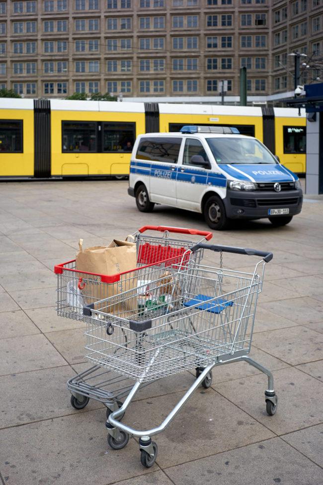 Zwei Einkaufswagen vor einem Polizeiauto