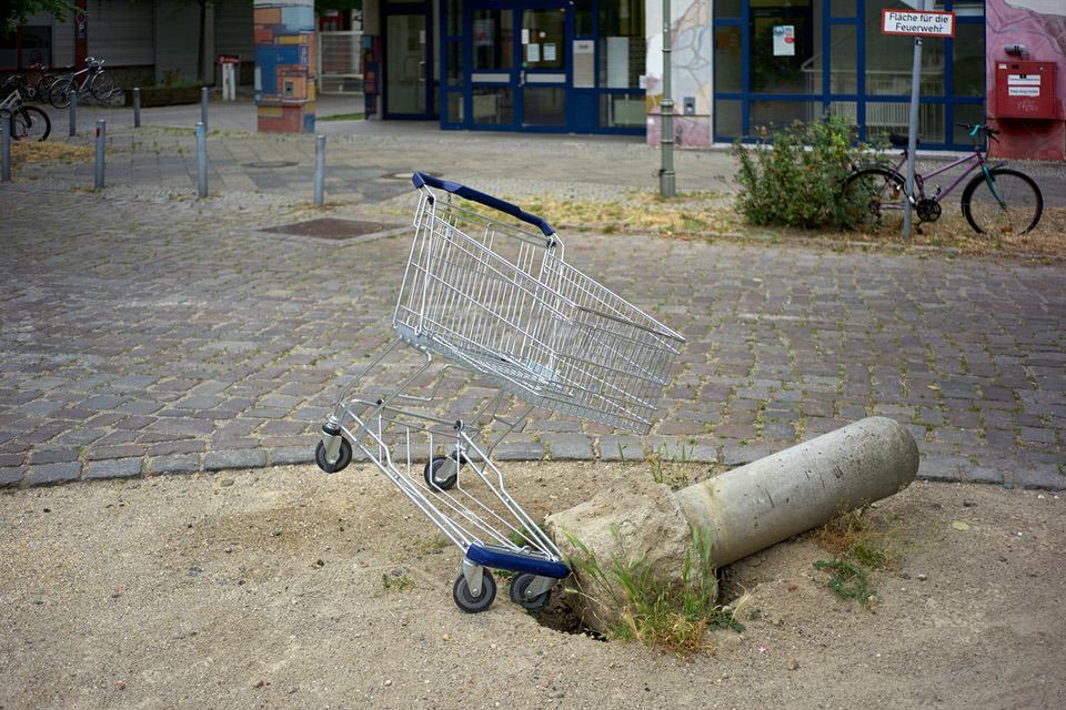 Einkaufswagen an einer umgekippten Säule