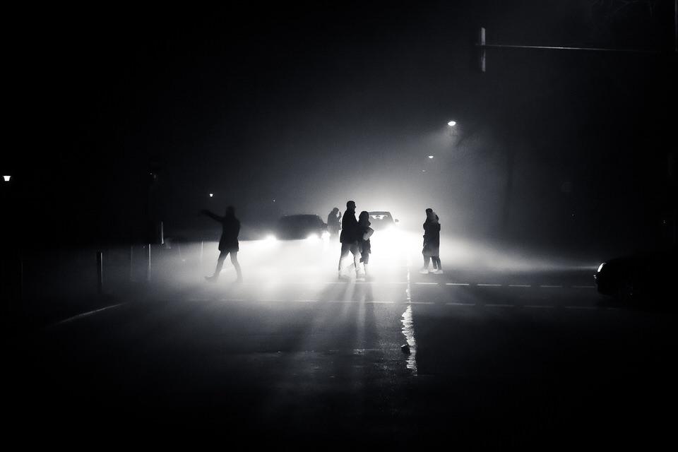 Menschen auf einer nebligen Straße im Schein von Autoscheinwerfern