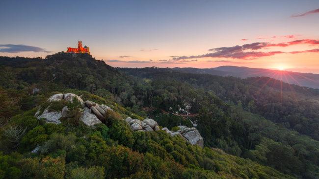 Landschaft mit Burg auf einem grünen Hügel