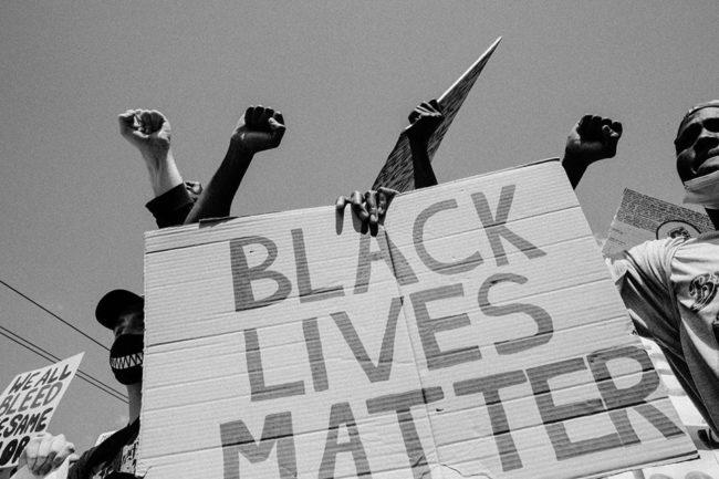 Menschen halten ein Plakat mit der Aufschrift Black Lives Matter