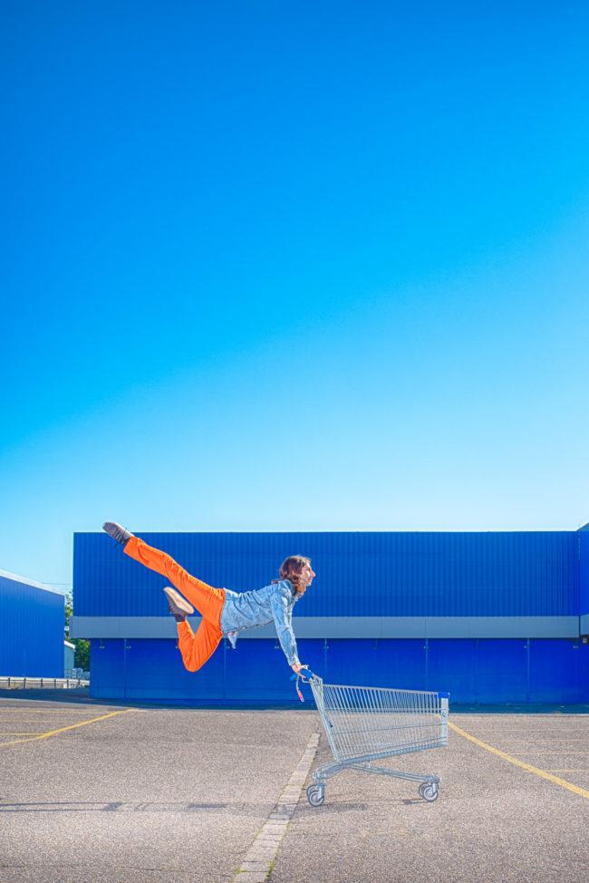 Person springt an einem Einkaufswagen nach oben