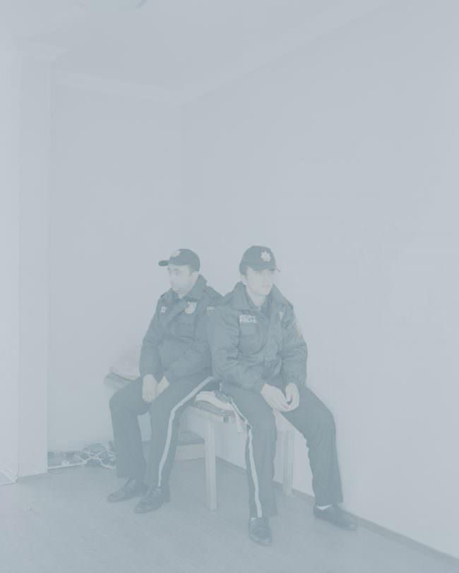 Zwei Polizisten sitzen auf einer Bank in einem Zimmer