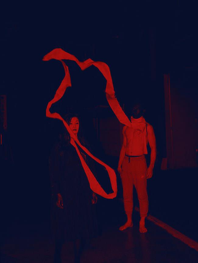 Zwei Menschen in rotem Licht sind mit einem Band verbunden