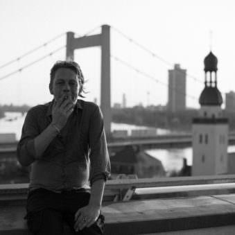 Person raucht vor einem städtischen Hintergrund