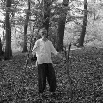 Person mit Holzstöcken im Wald stehend
