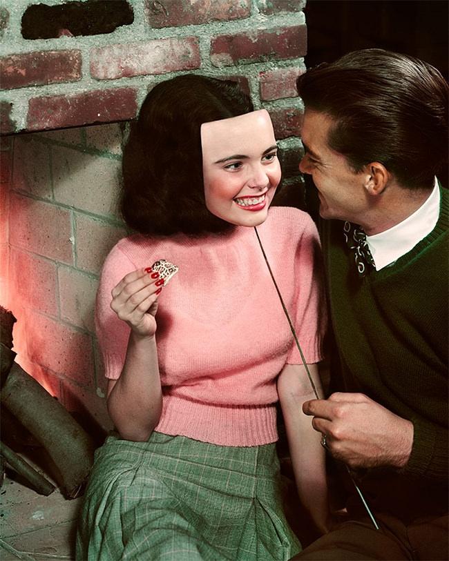 Paar vor einem Kamin, während er ihr eine lächelnde Maske vor das Gesicht hält.