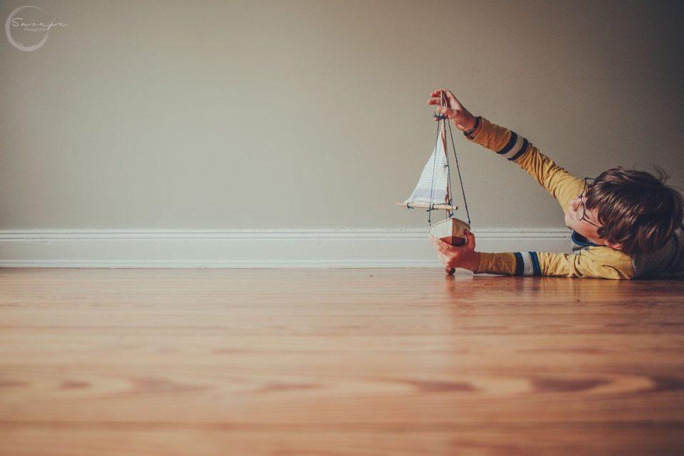 Kind spielt mit Spielzeugschiff in einem Zimmer