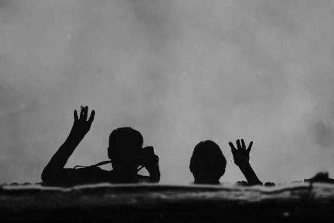 Silhouetten von zwei winkenden Menschen