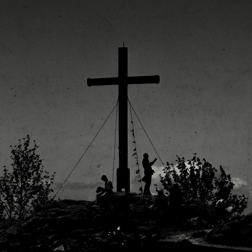Menschen an einem Gipfelkreuz im Schattenriss