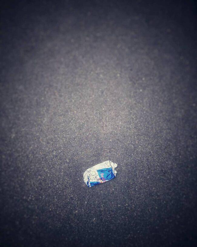 Eine zertretene Dose Redbull auf Betonboden