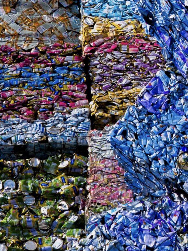 hunderte zerpresste Dosen nach Farben sortiert auf einer Müllhalde