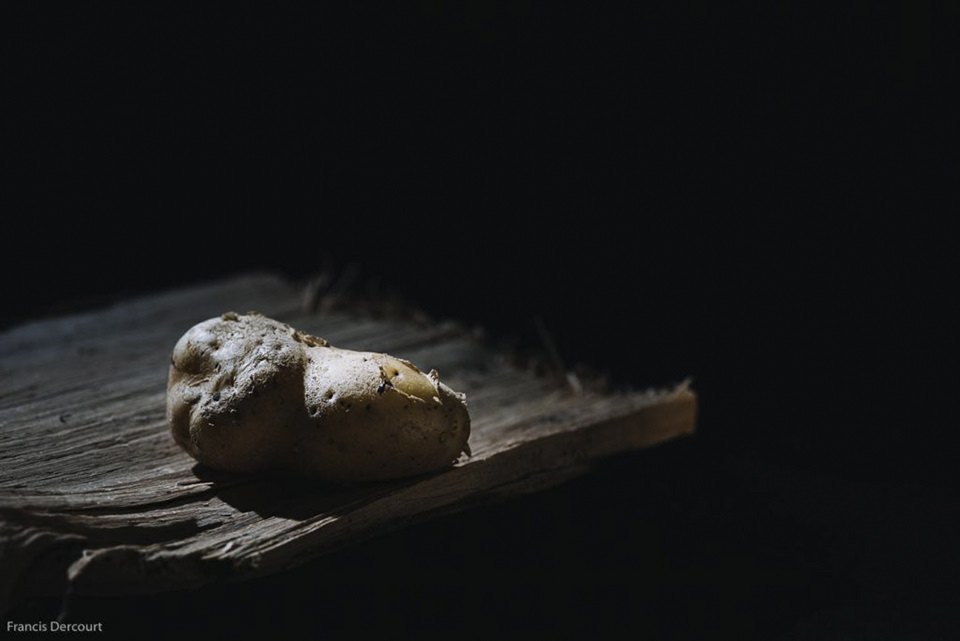 Eine Kartoffel auf einem Holzbrett in dunkler Umgebung
