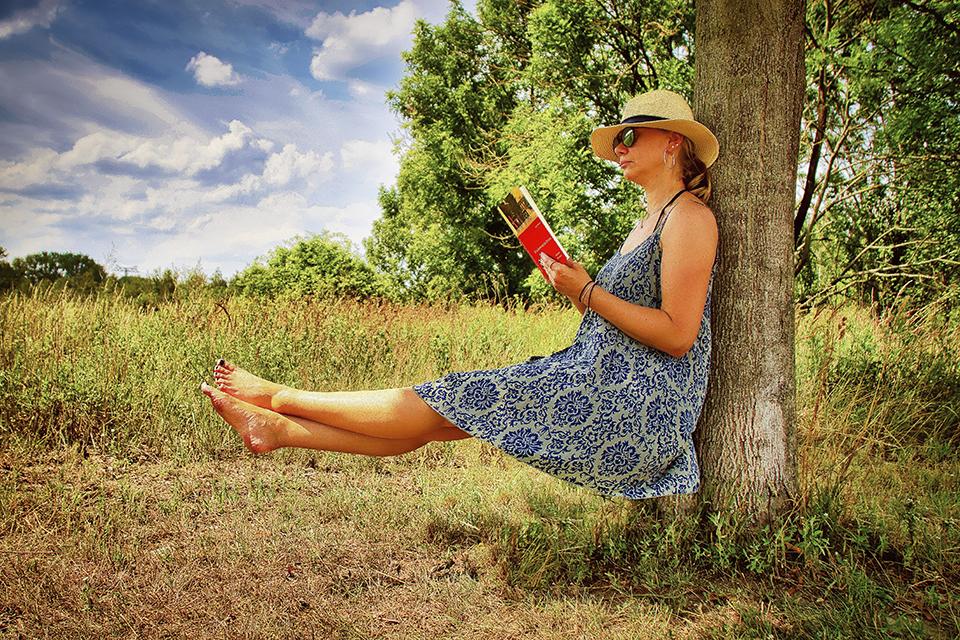 Eine Frau schwebt sitzend mit einem Buch an einem Baum