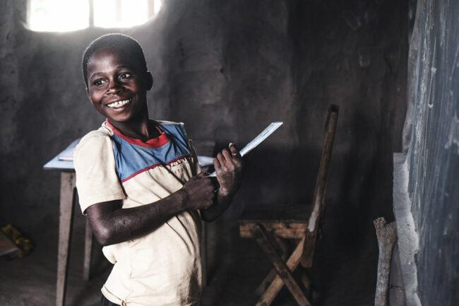 Lächelnder Junge steht mit einem Schreibheft an der Tafel