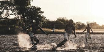 Jugendliche spielen Fußball auf sandigem Boden