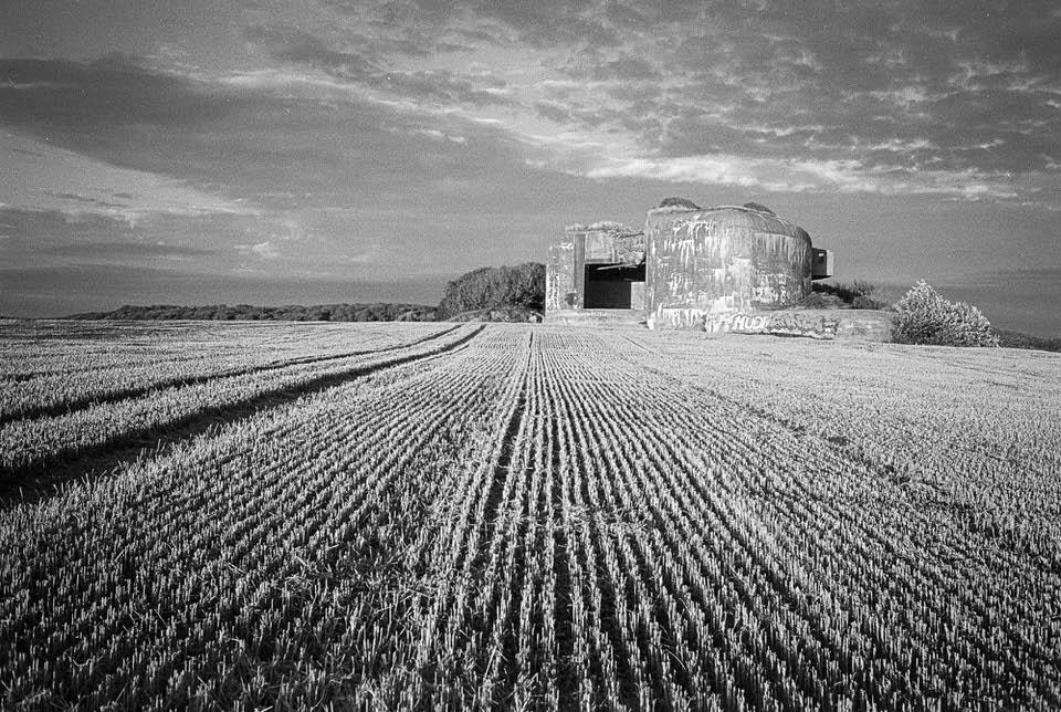 Im Vordergrund ein Feld, dahinter ein Bunker