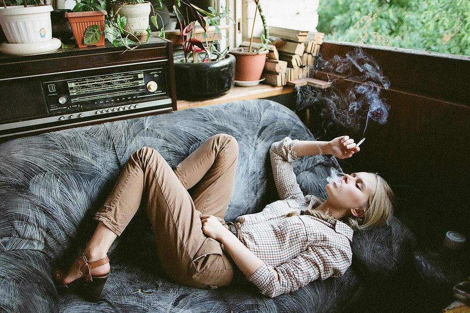 Rauchende Frau liegt auf einem Sofa, dahinter steht ein altes Radio