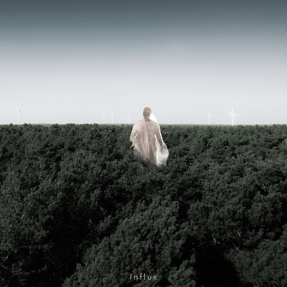 Eine Person ist umhüllt von einem Laken und steht in grünen Büschen
