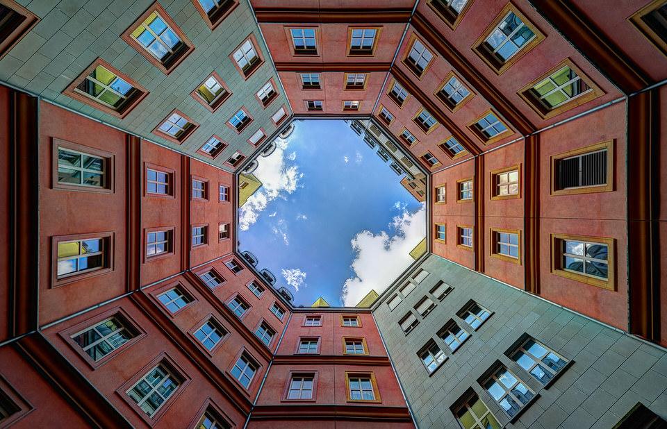 Blick nach oben durch Häuser auf einen blauen Himmel