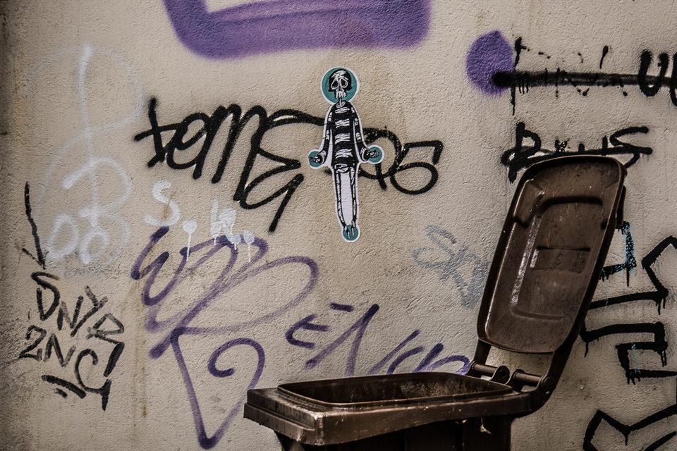 Grafitti an einer Hauswand darunter eine offene Mülltonne