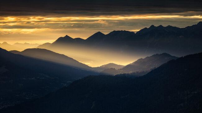 Dunst über Berghängen im Sonnenaufgang
