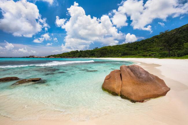 Stein am Meer mit türkisfarbenen Wasser und blauem Himmel