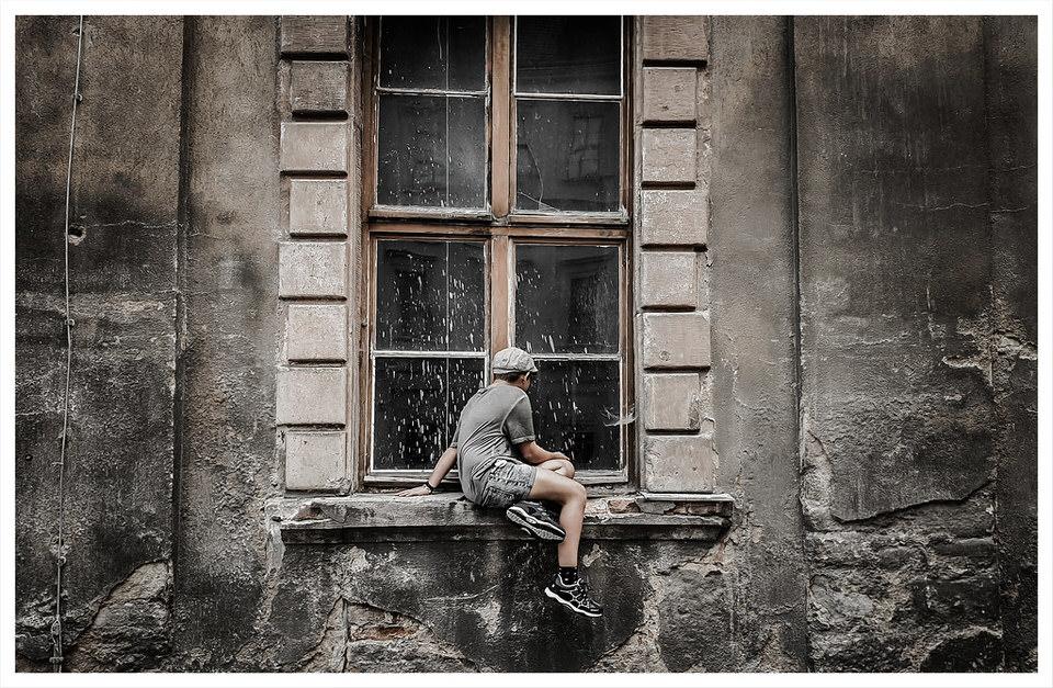 Kind sitzt auf einer Fensterbank und sieht in ein schmutziges Fenster