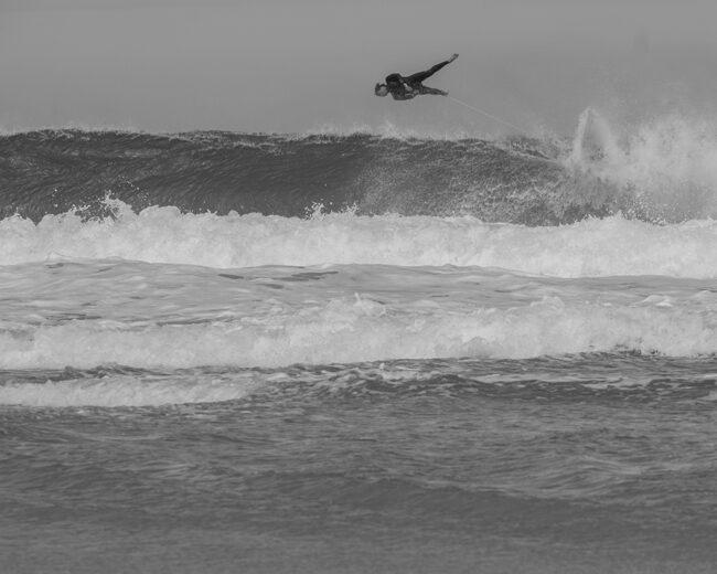 Surfer fliegt quer über der Welle