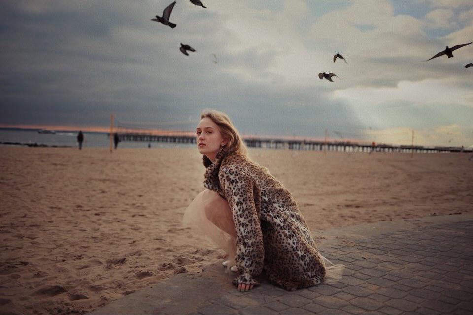 Eine Frau sitzt im Kleid und gemusterter Jacke am Strand
